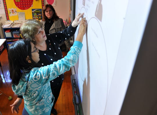 Angela Bender, then principal of Grant School, looks on as teacher Deanna  Griffin helps a student in 2012.