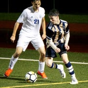 South Lyon's Cade White, right, spun around to his right on this play and scored the Lion's first goal against Walled Lake Western.