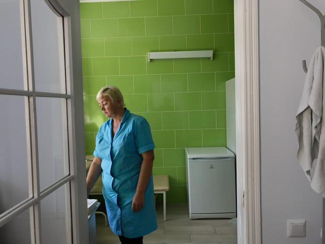 A nurse at a public clinic in Kharkiv gets ready to attend a patient.