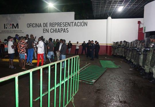 Migrantes de origen africano protestan ante la vigilancia de policías militares en la madrugada de este jueves, en la garita Siglo XXI de la ciudad de Tapachula, estado de Chiapas (México).