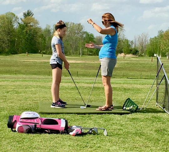 Golfer Madison Bajis gets instruction from Wendy Palmateer on May 18, 2017, at Golf Country & Pro Shop in Kimball.