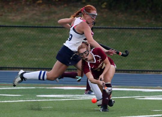 Arlington's Emily Strutt (14) moves the ball away from John Jay's Marissa Lavery (19) during field hockey action at John Jay High School in East Fishkill Oct. 2, 2019.  John Jay won the game 2-1.