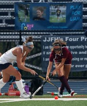 From left, John Jay's Serena Marchi (22) and Arlington's Rory McComb (7) battle for ball control during field hockey action at John Jay High School in East Fishkill Oct. 2, 2019.  John Jay won the game 2-1.