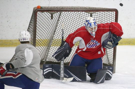 Americans' goalie Andrew Hammond gets an arm on a shot from Tyler Randell.