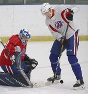 Rochester Americans' RW Tage Thompson, right, tries to deflect a shot from the point past goalie Andrew Hammond during their practice at the Bill Gray's Regional Iceplex in Brighton Thursday, Oct. 3, 2019.  The Amerks kick off their season with their home opener Friday, Oct. 4, against the Syracuse Crunch.