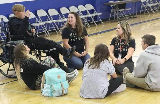 Catalyst Mentoring program director Jenna Berry, center, and volunteer mentor Beckie Luff listen to student Maddux Morley, left, during a lunchtime mentoring session at Turtle Bay School on Wednesday, Oct. 2, 2019.
