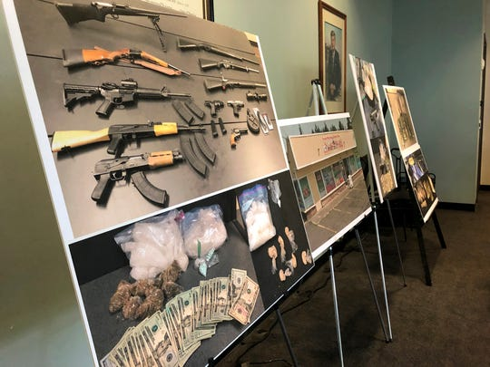 Photos of guns, drugs, and money are displayed at a news conference, Wednesday, Oct. 2, 2019, in Portland, Ore. U.S.
