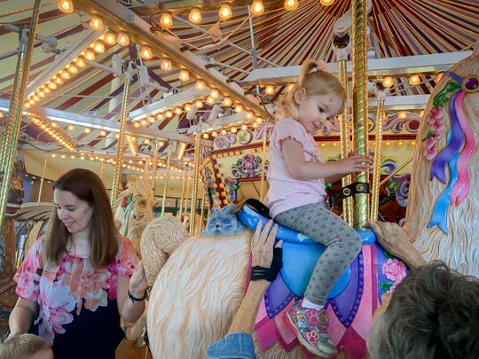 Elliana Bowdoin, 3, of Salem, is photographed being helped up on an animal by her grandmother Carolyn Voss as she gets ready for her ride on the carousel.