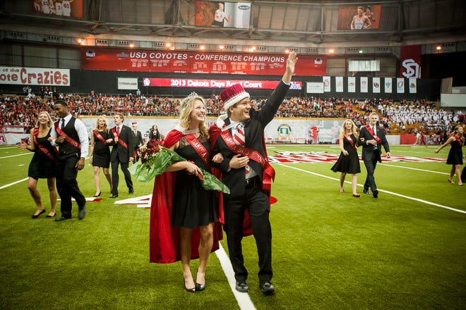 Anna Hyronimus of Valley Springs and Gavin Pochop of Gregory saluting the crowd following the halftime coronation ceremony at the University of South Dakota's Dakota Days football victory over Missouri State.