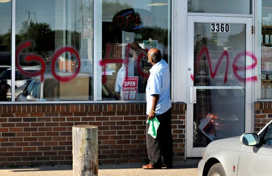 In this July 2010 file photo Hormud Market owner Hared Jibril removes grafitti from the front of the store in St. Cloud.