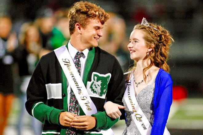 In this Friday, Sept. 27, 2019, photo, Deserae Turner stands with Case Gehring as the Homecoming Court is announced during halftime of Green Canyon's football game in North Logan, Utah. Turner, a Utah high school student who survived a gunshot wound to the head was named homecoming queen by her classmates. Turner was found in a ditch after being shot in the back of the head and left for dead by two classmates in February 2017. (John Zsiray/5150photos.com via AP)