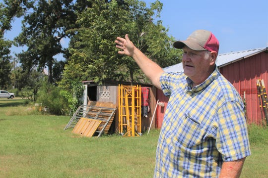 Rex Chambliss gestures to the front of his house where nine cedar, pine and pecan trees were ripped out of the ground during Hurricane Michael.