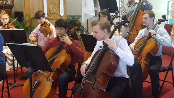 Thomas Miller, left, and Leif Clark rehearse with the Youth String Orchestra at the First Presbyterian Church of Vero Beach.