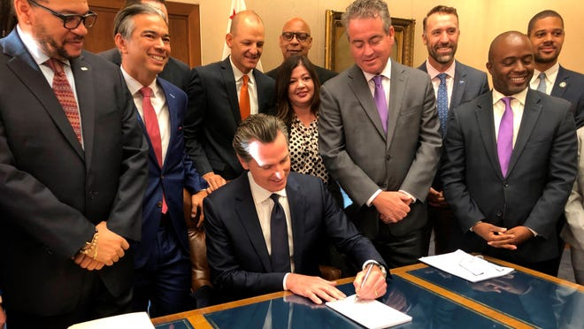 California Gov. Gavin Newsom signs a law overhauling charter schools on Thursday in Sacramento. The law gives school districts more authority in deciding what charter schools are allowed within their boundaries.