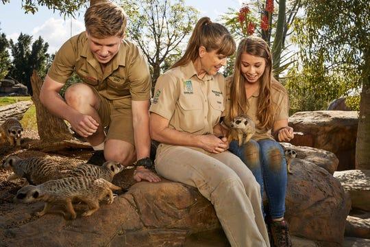 Bindi Irwin, Terri Irwin and Robert Irwin with meerkats.