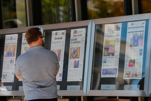 A man stops to look at newspaper front pages from around the US on display at the Newseum in Washington, Sept. 25, 2019. House Speaker Nancy Pelosi, D-Calif., announced on Sept. 24, 2019 she will launch a formal impeachment inquiry against President Donald Trump. A whistleblower's complaint alleges President Trump pressured the President of Ukraine to investigate Joe Biden to help the President's 2020 reelection bid.