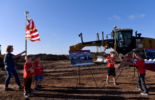 Students from Taylor Elementary School right a photograph that had blown over in Wednesday's wind during the ground breaking for their new school.