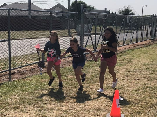 Kassidy Kelley, left, joins classmates Dawn Celeste Cannon and Avriell Perez, fourth-grade students at Dyess Elementary, for a lap around the school's makeshift course Oct. 4. While every Friday is running day at the school, this run was extra special because it served to raise awareness for cancer, including breast cancer symbolized by the pink ribbon.