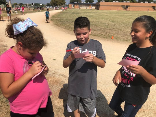 Fourth-grader Haylee Cogar, left, marks another lap around their school's running course complete with classmates Samuel Stroman and Nevaeh Solis at Dyess Elementary.