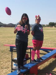 Dyess Elementary physical education teacher Lyana Lafuente shows her fourth-grade students how to mark a lap complete on their sheets of paper before they ran around the school's makeshift course Oct. 4. Lafuente organized the run Friday to honor breast cancer survivors and those who've lost the battle, while selling shirts to help make an $823 donation to Hendrick Medical Center's The Hope Fund.