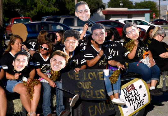 Eagle Moms hold cutouts of their player's faces while riding a trailer during Thursday's Abilene High School's homecoming parade on North Sixth Street.