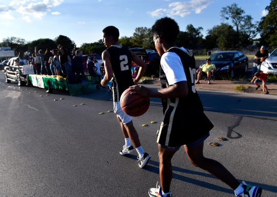 Basketball players dribble on North Sixth Street during the Abilene High School's homecoming parade.