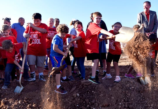 Students from Taylor Elementary School shovel dirt as they partake in a groundbreaking ceremony for their new school Wednesday.