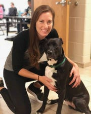 Pennfield High School Phys Ed teacher Molly Collins with Brody James, a 2-year-old black lab mix and certified therapy dog.
