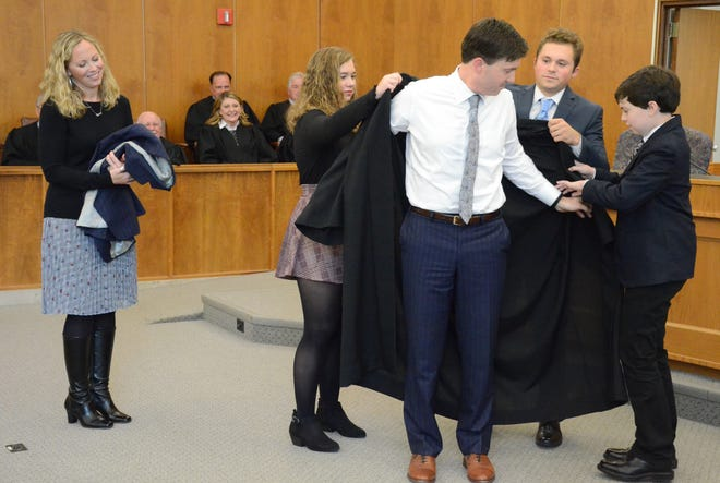 As is wife, Margie watches, children Katie, 15, Jonathan, 17, and Jackson, 11, help District Judge Jason Bomia with his robe.