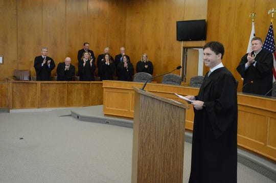Other judges stand to applaud at the investiture of District Judge Jason Bomia.