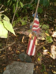 An ancient flag adorns a stone in Stratford Cemetery in Scranton.