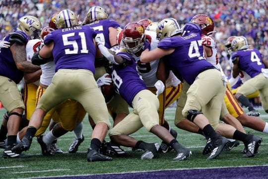 Washington's Richard Newton, center, carries the ball in the first half of a game against USC in Seattle on Sept. 28, 2019. (AP Photo/Elaine Thompson)