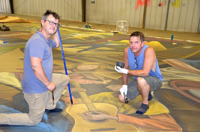 Jeremy Russell, left, and Scott Allred, or Brushcan Murals, work on 30-foot by 50-foot mural that will go up on the exterior wall of the Black Mountain Center for the Arts at the end of October.