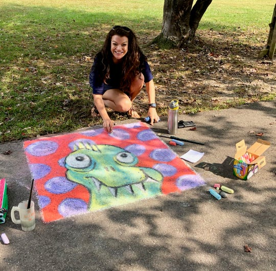 Owen High School art teacher Lacey Brown shows off her sidewalk chalk creation at Veterans Park on Sept. 28, during a dedication ceremony for a new sculpture by Julia Burr and Dana Gingras.