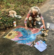 Libba Tracy puts the finishing touches on her chalk art during a dedication ceremony for a new sculpture in Veterans Park on Sept. 28.