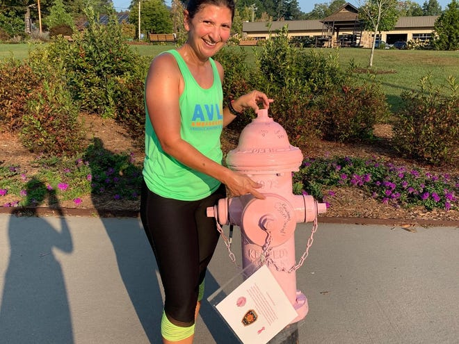 Breast cancer survivor Crystal Shirk signed one of 12 pink fire hydrants around downtown Black Mountain for the Breast Cancer Awareness Month. The hydrants, which can be signed by anyone, will be pink throughout the month of October.