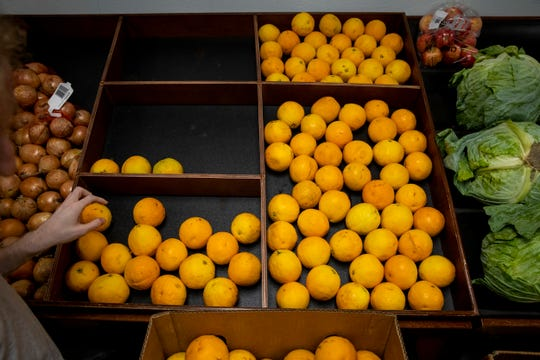 Valentine Peterson stocks oranges at Fuel NKU, a food pantry at Northern Kentucky University Monday, September 30, 2019 in Highland Heights, Kentucky.