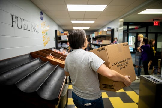 Angela Anderson restocks Fuel NKU with bathroom tissue that the Freestore Foodbank delivered Monday, September 30, 2019 at Northern Kentucky University in Highland Heights, Kentucky. Anderson is a research coordinator at Fuel NKU.