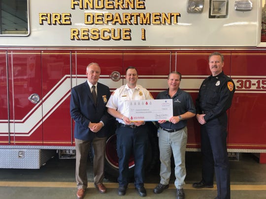 Roger Shaffer, senior manager of Field Operations for New Jersey American Water (second from right), presented a check for $960 to representatives from the Finderne Fire Department in Bridgewater.