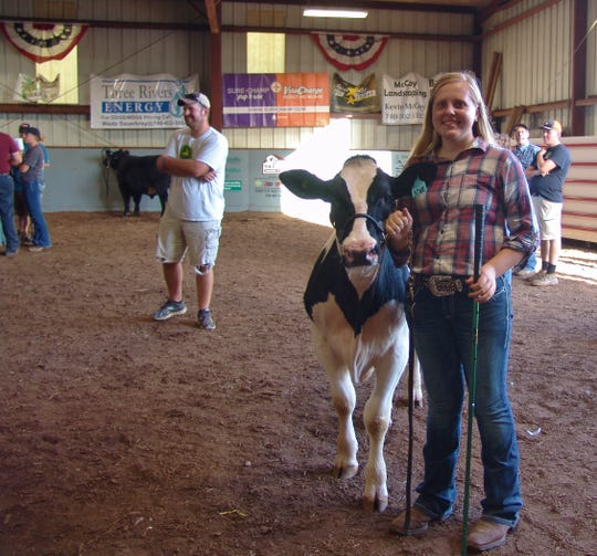 Michaela Greten poses with her Grand Champion dairy feeder calf during the Sale of Champions auction Thursday in Hunter Arena. Hunter Farms purchased her calf, and Michaela said she will put the money toward college.
