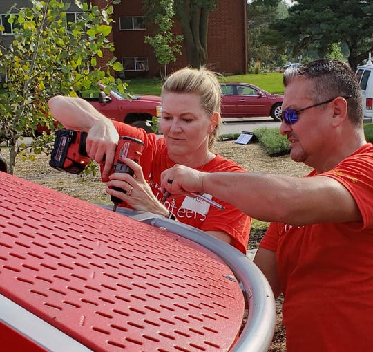 Wells Fargo employees Kris McNutt and Ben Dorrance install playground equipment at Whitmer Park in Des Moines.