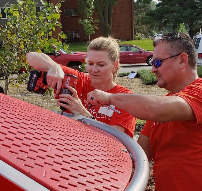 Wells Fargo employees Kris McNutt and Ben Dorrance install playground equipment at Whitmer Park in Des Moines.