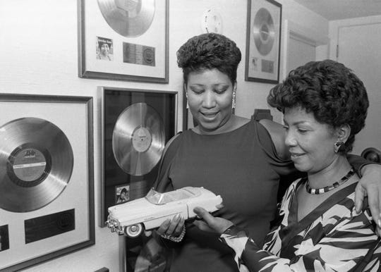 "Aretha and her sister Erma admire a gift, a pink Cadillac, from Narada Michael Walden, the producer and composer of ""Freeway of Love."" The two are in Aretha's bedroom hallway. The walls are covered with gold and platinum records. The photo is one of many included in Linda Solomon's new book, ""The Queen Next Door."""