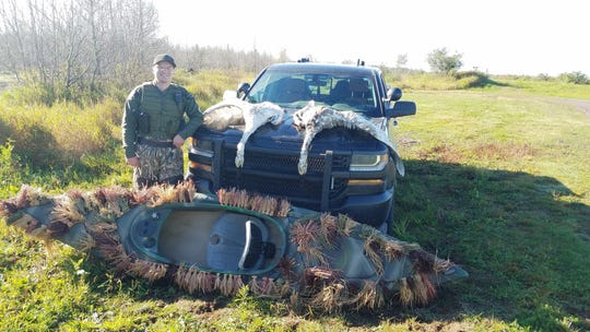 Conservation Officer Cody Smith is pictured with two trumpeter swans poached on Sept. 28, the opening day of waterfowl hunting season in the Upper Peninsula.