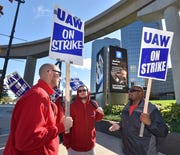 UAW Local 163 union members Stephen Alfaro of Southfield, Ryan Pappas of Taylor and Jeremy Council of Romulus, picket in front of General Motors Co. Renaissance Center in Detroit.
