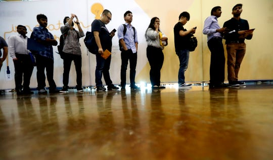 Job seekers line up to speak to recruiters during an Amazon job fair in Dallas.