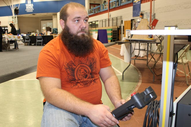 Lucas Weiner, a maintenance supervisor at Tower Automotive, works the controls on a collaborative robot Thursday at the Sandusky County Economic Development Corporation's Manufacturing Day Open House. The event was held in conjunction with SCEDC's THINK Manufacturing Showcase, which took place Friday at Terra State Community College.