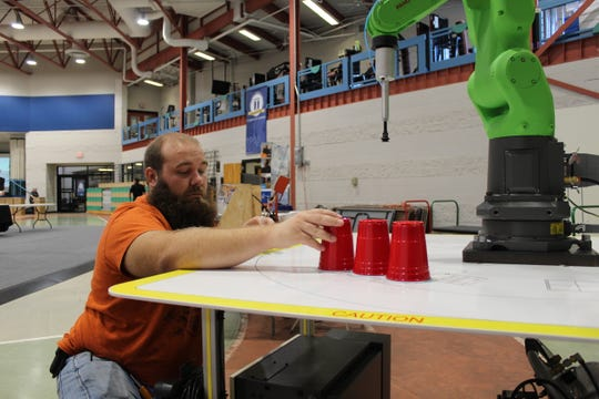 Lucas Weiner, a maintenance supervisor at Tower Automotive, positioned red cups on a table and used a controller to move a collaborative robot Thursday at the SCEDC Manufacturing Day open house.