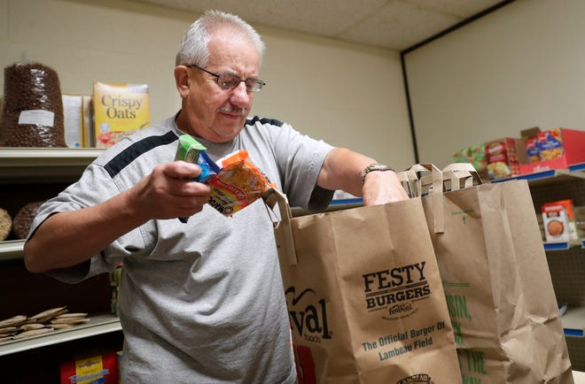 Volunteer Wayne Leiterman of Sobieski bags donations on Oct. 1, 2019, at Trinity Lutheran Church's food pantry in Green Bay, Wis.