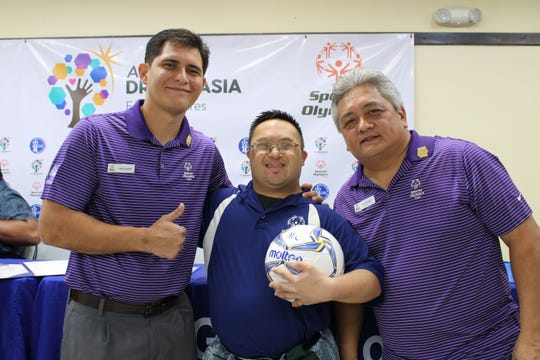 Special Olympics Guam executives Camilo Lorenzo, left, and Paul Mendiola, right, with an athlete after a press conference at the GFA National Training Center announcing the creation of Unified Soccer for all athletes, in line with Special Olympics International's inclusion movement evolution.